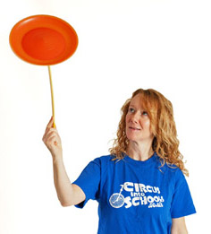 Image of a Circus Tutor teaching spinning pkate at a  Circus Skills Workshop in Cornwall