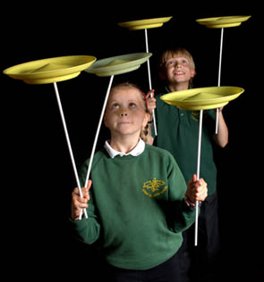 boys spinning plates at a circus workshop