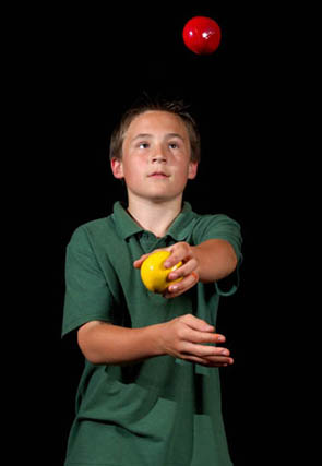 Boy learning how to juggle 3 balls
