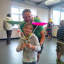 A picture of a girl spinning a plate with her dad at a Circus Skills Workshop