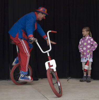 Spangles te clown trying to ride a broken bike during a clown show, a small girl looks on to the side.